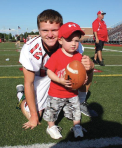 Hunter Van varsity quarterback shows Cody Roy how to throw.