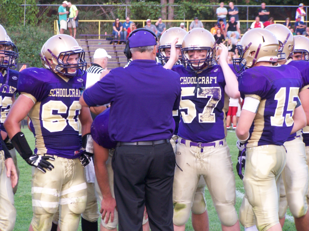 Coach Terry Haas goes over strategies with his defense during a timeout in the Sept. 6 contest against Constantine.