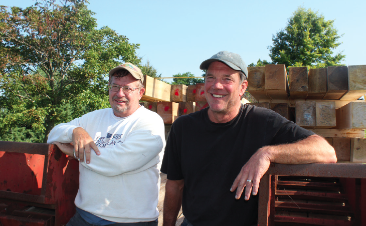 Bob Smith and Richard Barnes loaded timber for the frame that came from Mike and Kathy Bechers' woods. After the job was done they relaxed on the huge trailer load of wood.