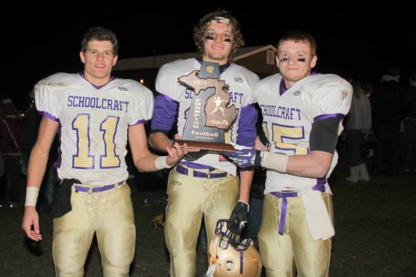 Brenan Vaughn #11, Kyle Santman #21, Charlie Schultz #15 accept the District Title trophy.