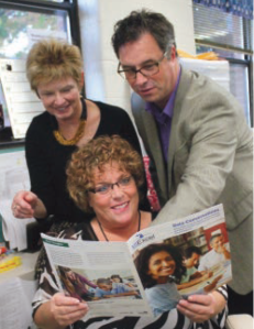 Jamie Masco, an instructional consultant at SunsetSchool who helped forge the plan for improvement along with Principal Pat Moreno and Grant Chandler of the MSU College of Education, look over the brochure that describes the focus school effort at Sunset Lake School.