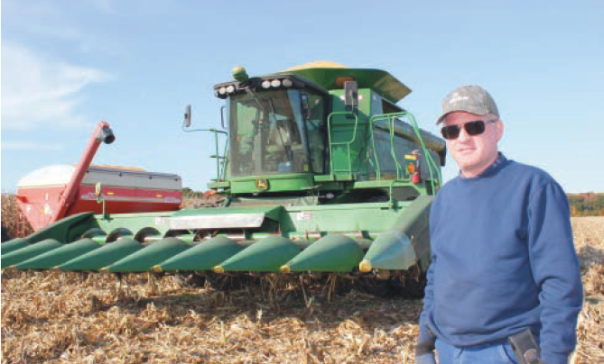 Todd Weinberg stands in front of the huge combine that can harvest a big corn field in less than a day.