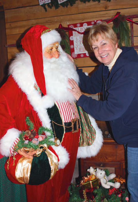 Mardee Mott with statue of Santa that greets guests as they walk in the front door of the Christmas Barn.