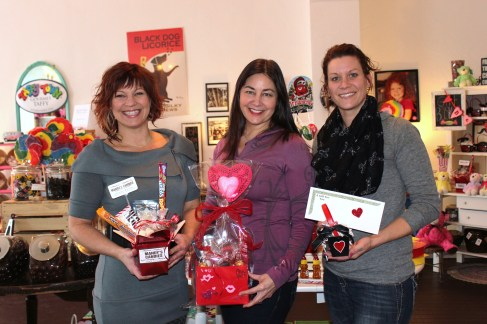 Shawn Verner Crotser, Mandy Kokales, and Mandy Miller hold some of the special Valentine's Day gift basket combinations the two businesses have put together. They are next door to each other on South Main in Vicksburg in what they are joyfully calling Mandy's Corner, thus doing some joint marketing of their products.