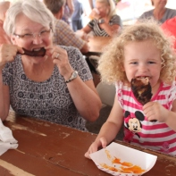 Diana Girolami with her granddaughter sample BBQ chicken and pork ribs.