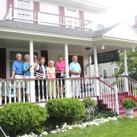 Family and friends congregate on the porch of Salli and Bill Carter's home to watch the parade form up on Eliza Street in Schoolcraft.