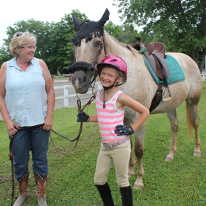 Cheri Lutz helps her granddaughter Tayler Lutz get ready to ride Hailey, their leased horse at Lou Don Stables.
