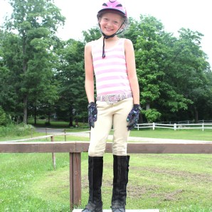 Tayler Lutz stands on her mounting box in order to get up on her 1,200 pound horse, Hailey.
