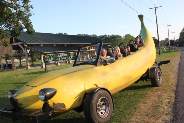 The Banana Car will make an appearance at the Vicksburg Farmers' Market on August 21 to give free rides, sponsored by SC Enterprises. The passengers seen here are Tom Brown, Alyssa Kirby, with Taigen and Brady Copeland toward the back.