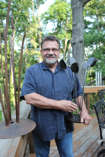 Brian Brook holds one of his metal sculptures that he sells at area art shows.