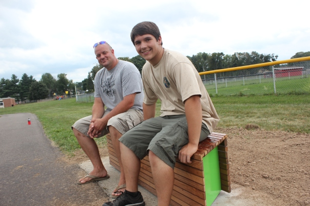 From left: Lucas Hilliard and Tanner White occupy the newest of three benches built as rest stops on the walking track at Sunset School. White did this in partnership with the PTA as part of his Eagle Scout project. The bench has a concrete pad with the finest lumber he could find to purchase for the three benches, so they will last at least through his lifetime, he said.