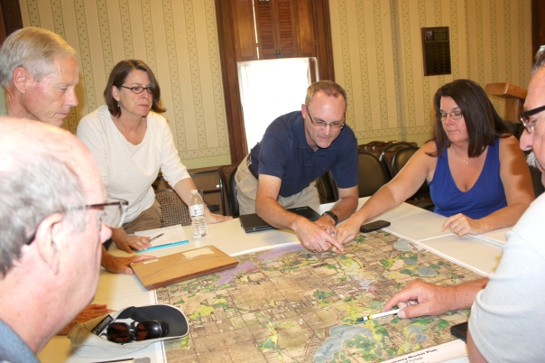 From left: Ron Smith, Bill Deming, Julie Merrill, James Earl, Kathleen Hoyle, and Ken Schippers review the map of the proposed trail through the village of Vicksburg.
