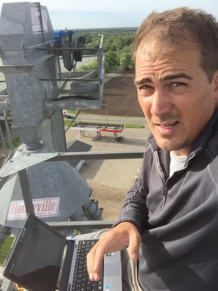 Andy DeVries atop the H & H Feed and Grain tower where his company Digital Example, LLC, also has a transmitter, and offers subscriber Wi-Fi service to residents who do not have Comcast availability.