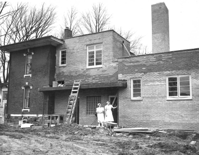 Greta Simmons on the right and an unidentified nurse on the left, survey the addition being built to the Franklin Memorial Hospital in the 1950s.