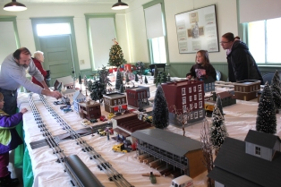 Adults love model trains as much as kids. Joe Timko shows visitors the display at the township hall in the Historic Village. The trains will be running from 10 a.m. to 5 p.m. on Saturday, December 5, as well as the two Saturdays following. The buildings are modeled after Vicksburg village stores and businesses downtown.