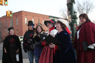 Choir members from the Vicksburg United Methodist Church Choir serenade Christmas visitors.