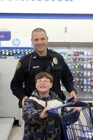 Vicksburg Police Officer Henry Kite, takes a youngster shopping for Christmas gifts.