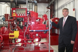 Mike Frederick of Frederick Construction, the Vicksburg company that built the new Eimo building, stands by the fire suppressant equipment that can act as a backup to village fire trucks.