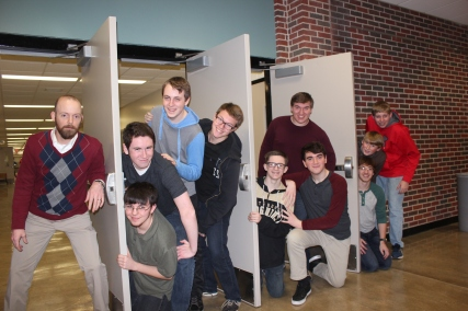 Simply Men, the Vicksburg High School chorus will perform as an integral part of the 2016 Showboat. Featured here behind the doors from left to right: Dustin Morris, choir director; next door at the bottom of the pile, Scott Gilbert, above him is Jakob Schmidt, then Matt Roop, and Seamus Hyman. Next door kneeling is Will Orchel, Logan Workman, in back is Caleb Dziepak. On the end, kneeling is Andrew Phelps, Jess Schmidt, Luca Cannizzaro. Not pictured but members include Alex Cannizzaro, Nathaniel Chiu, Will Cober, Brett Moore, Luke Piper, Alex Smith.