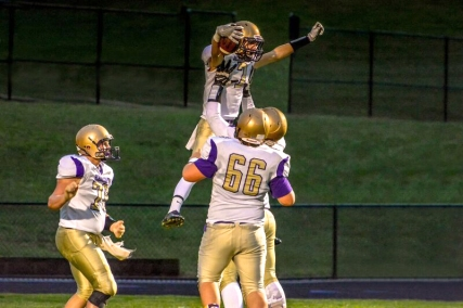 Nolan Anspaugh celebrates one of his many catches in the end zone during the Lawton football game with his teammates.