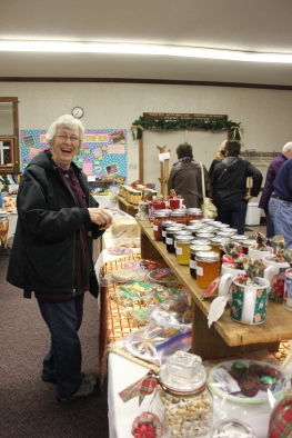 Lori Lash inspects the church's homemade bake goods, knitted items, jams and jellies that are for sale.