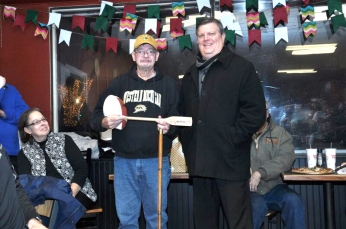 Bob Smith holds his P.J. Fleck autographed football and his 'Row the Boat' paddle presented by Robin Hook, assistant athletic director from WMU.