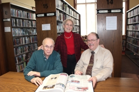 South County News board members Bob Ball on the left and Sue Moore standing, combined to present a bound copy of the three and a half years of the South County News publications to John Sheridan, Vicksburg District Library's director. He plans to place the volume in the history room of the library where the 125 years of bound volumes of the Vicksburg Commercial-Express are held. This tradition of binding the newspaper was begun by the early publishers, Meredith and Bernice Clark and carried on by Jackie and Warren Lawrence when they owned the newspaper. Moore was recruited to start the South County News in 2012, saying she would stick around to write and design three issues and then give way to an editor that the board would hire. It hasn't quite worked out that way as she has stayed deeply involved as editor and publisher over the last four years. She is a graduate of Michigan State University with a degree in journalism, with an emphasis on history and political science. Ball graduated from the University of Michigan with a journalism degree and worked for many years as editorial writer for the Royal Oak Tribune. He moved from Reading, Michigan to Vicksburg when he married Rachel Freeman and now serves as this newspaper's copy editor.