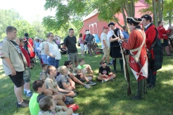 Re-enactors from the North West Territory Alliance tell stories about the Revolutionary War to eager listeners in the Historic Village.
