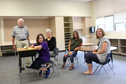 Gabe Redmond is seated at a desk in a classroom inside the Schoolcraft Early Elementary building. Standing and seated in back of him from left to right are Sr. Jack Sauer, Sue Hendriksma, Paige Reid and Darcy Bolles. All of the people pictured attended school in this building at one time or another.