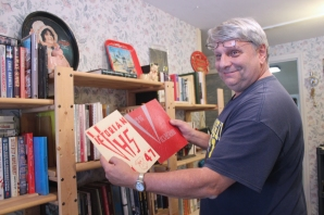 Denny Olson displays Vicksburg High School yearbooks from his collection.
