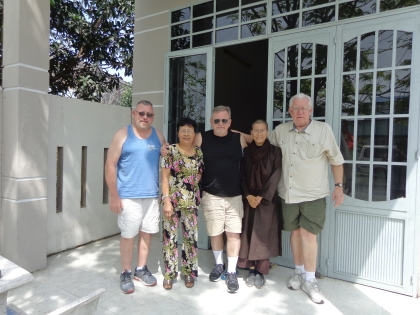 """Gary Belden, in the middle, visited Vietnam with friends from his platoon. Joe Oncay is on the left and Bob Lingren on the right. They paid a special visit to """"Wendy"""" shown in the print dress. The other person is Chau, a Buddist nun."""