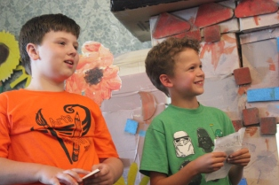 Christopher Carter and Ethan Bastos stand in front of the stage designed and created by the campers. They are rehearsing the skit that they wrote in Spanish during their language arts class.
