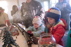 Children admire the O-gauge train display that was set up to resemble the village of Vicksburg in the Historic Village's old Township Hall.