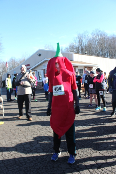 Runners, including this one dressed as a chili pepper, congregated in the parking lot of Vicksburg Auto Body shop on Spruce street before the 5K race, sponsored by the Vicksburg High School cross country team.
