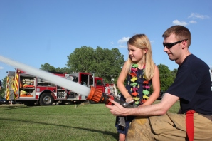 The village rolled out the police cars, fire trucks, and the sheriff brought emergency vehicles. Clara Stafinski was treated to a lesson on how to operate the firehose on a warm summer day.