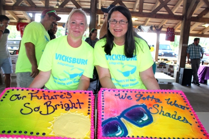 Jennie Holmes and Michelle Morgan show off the celebration cake that the village of Vicksburg served to visitors at its July 15 village council meeting.