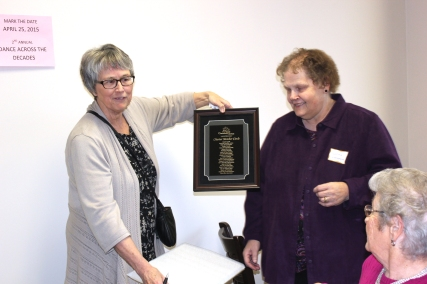 Danna Downing displays a plaque that lists the original Charter membership of South County Community Services in 2015. Lorna Landrum who was president then, is on her right.