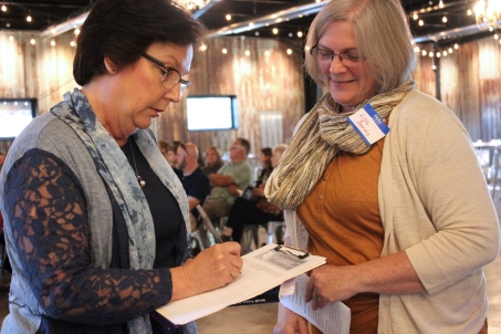 Carol Braymer, first prize winner in the Senior Poem category, signs in at the Tournament of Writers celebration with Lisa Beams on the right.
