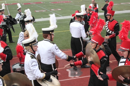 Band members from Vicksburg's drum line exchange handshakes with members of Western Michigan University's marching band following their drumline faceoff.