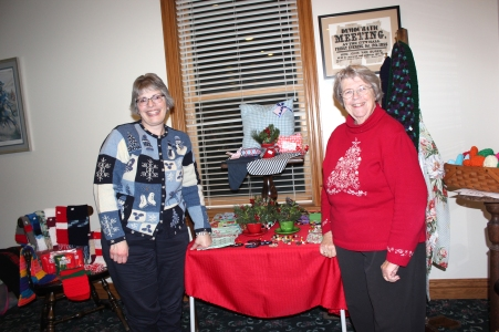 Michelle Romstadt and Nancy Rafferty display the craft items the Presbyterian Church women will have on sale at the DeVries law firm office on Grand Street.