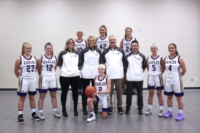 Varsity Basketball Kneeling in front: Allie Walther. Standing in second row from left: Alana Reed, Kayla Onken, Assistant Coaches Shelly Cochran, Kristin McNally, Head Coach Steve Kulczyk, Asst. Coach Max Kulczyk, Savannah Seath, Paige Reid. Standing in back from left: Gabi Saxman, Mackenzie Miller, Adrienne Rosey.