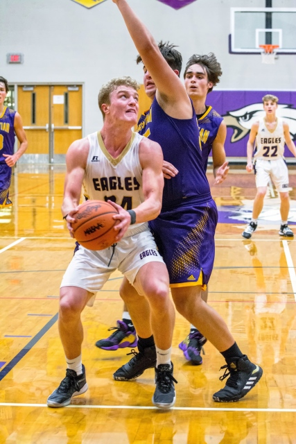 Schoolcraft's Trevor DeGroote, closely guarded by a Kalamazoo Christian player, looks to shoot. Jonny Abel, number 22, trails the play. Photo by Stephanie Blentlinger, Lingering Memories Photography.