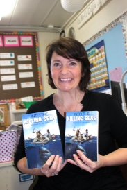 Jenny Taylor holds up copies of Into the Killing Seas by Michael P. Spradlin who will be featured at the Grand Battle of the Books on Feb. 20 at the Schoolcraft Performing Arts Center.