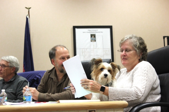At right, Cheri Lutz and her special dog, Teddy, at a Schoolcraft Village Council meeting.