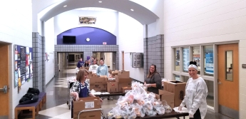 Schoolcraft volunteers help package food from their students in the hallway of the high school.